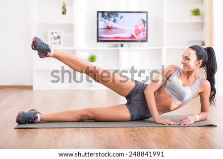 Fitness, workout, healthy living and diet concept.  Rear view of young woman is stretching on floor and watching tv at home. - stock photo