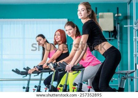 Fitness workout in the gym. Athletic girl pedaling on the simulator until her four girlfriends athletes pedaling on a stationary bike at the gym. - stock photo