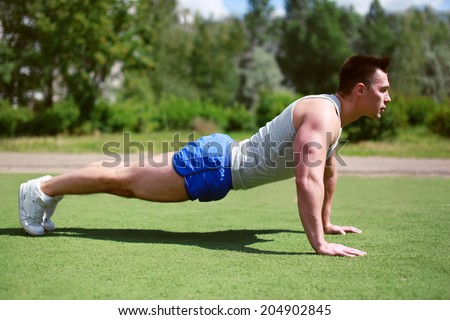 Fitness, workout, sport - concept. Sportsman push ups outdoors - stock photo