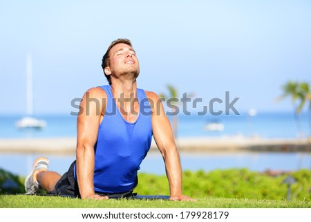 Fitness yoga man in cobra pose stretching abs stomach muscles. Fit male sports model doing stretching exercise outdoor in summer on grass. Handsome young male sports instructor. - stock photo