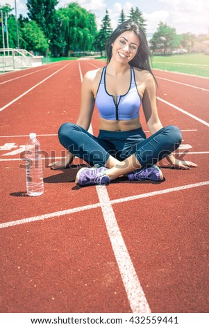 Fitness young adult woman taking break from running exercise during hot summer day with bottle of cold drinking water. Toned image. - stock photo
