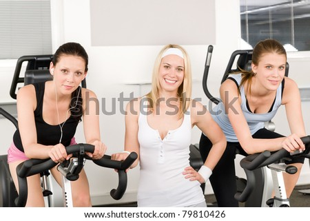 Fitness young girls on gym bike indoor cardio exercise posing