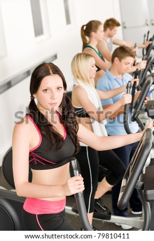 Fitness young group on elliptical cross trainer at health gym