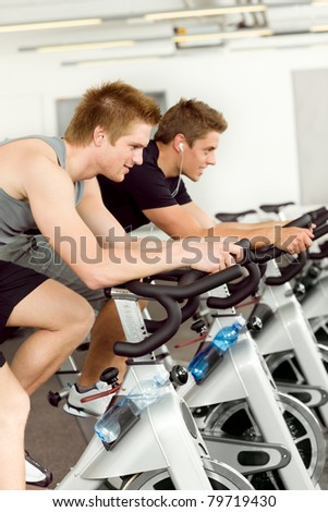 Fitness young man on gym bike indoor cardio exercise - stock photo