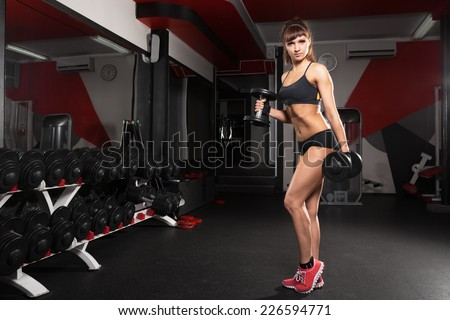 Fitness young sexy girl in the gym doing exercises with dumbbells
