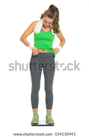 Fitness young woman checking body fat while standing on scales - stock photo