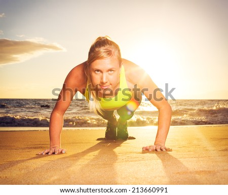 Fitness young woman doing push ups on beach at sunset. Outdoor workout. - stock photo