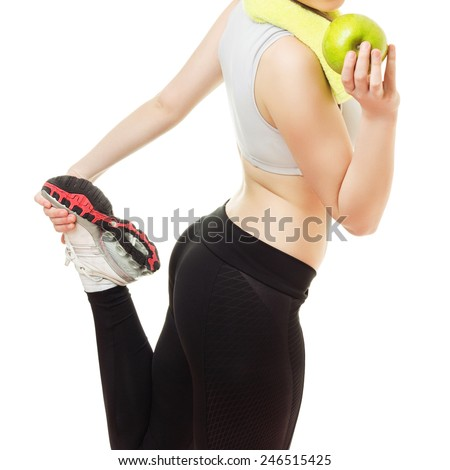 Fitness young woman in running shoes holding apple. Closeup shot of fitness girl in sportswear holding her leg up. Square format, isolated on white background, unrecognizable person, no filter. - stock photo