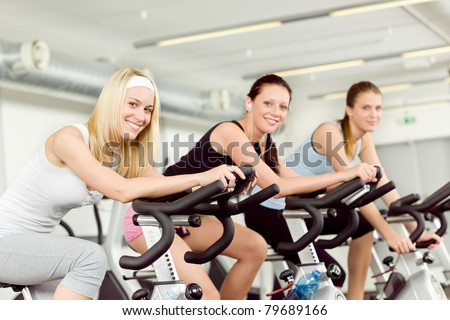 Fitness young woman on gym bike indoor cardio exercise - stock photo