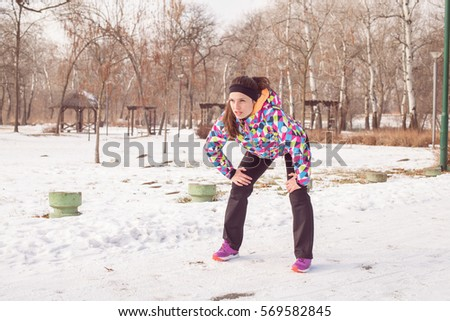 Fitness young woman relaxing after exercise outdoor, winter season healthy activity.
