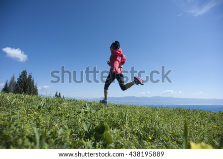 fitness young woman trail runner running on beautiful mountain peak