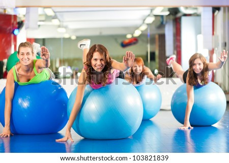 Fitness - Young women doing sports training or workout with gymnastic ball in a gym - stock photo