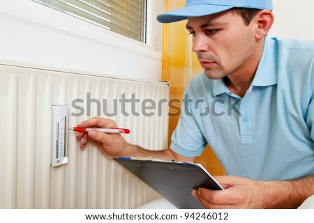 fitter with radiator. energy savings. reading the heating - setting. - stock photo
