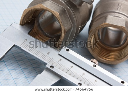 fitting and callipers  on a background of graph paper - stock photo