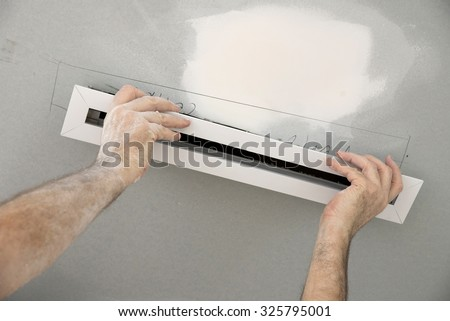 Fitting high tech vent to bathroom ceiling - stock photo