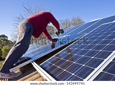 Fitting solar panels to roof of house - stock photo