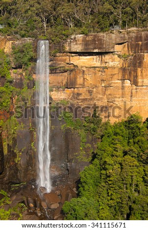 FITZROY FALLS, MORTON NATIONAL PARK, NSW, AUSTRALIA - December 20, 2014: Fitzroy Falls - famous Australian waterfall with 80 m drop of water plunging from sandstone rocks - portrait layout