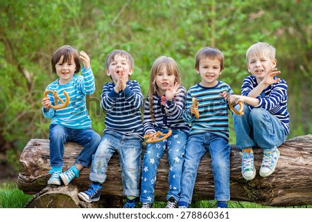 Five adorable kids, dressed in striped shirts, sitting on wooden tree trunk, eating pretzels for afternoon snack, smiling and chatting - stock photo
