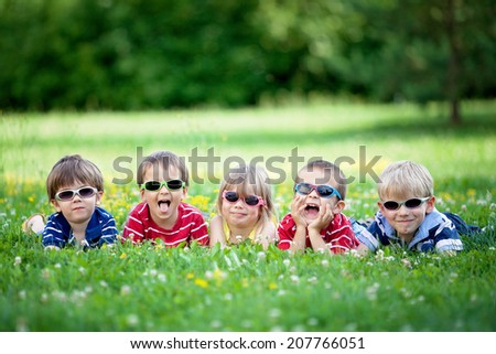 Five adorable kids, lying on the grass, smiling, having fun, wearing glasses - stock photo