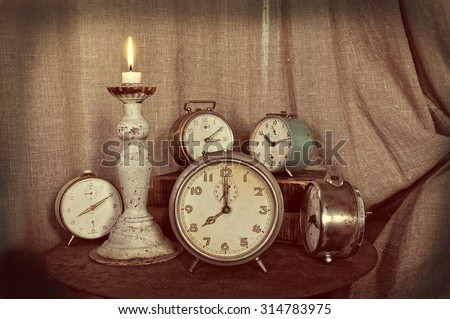 Five alarm clocks on a night stand with candle light, vintage style. - stock photo
