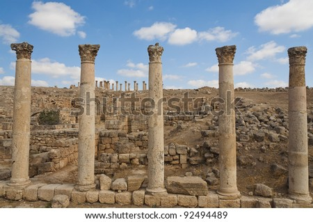 Five ancient vertical columns with capstones along the Roman road in Jerash, Jordan - stock photo