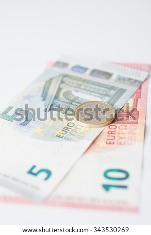 Five and ten euro note with euro coin - stock photo