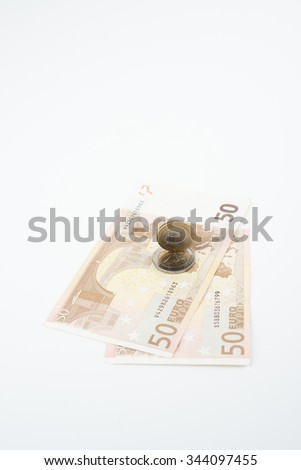 Five and ten euro note with euro coin lying on bank note - stock photo