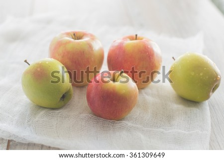 Five apples lay on the white textile