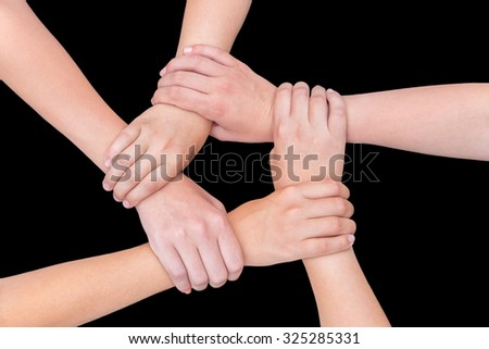Five arms with hands of girls holding each other joining on black background - stock photo