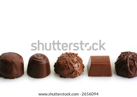 Five assorted chocolates in a row, isolated on white.