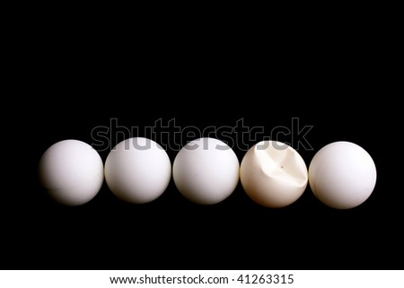 Five balls for game in table tennis on a black background. One ball is rumpled in game.