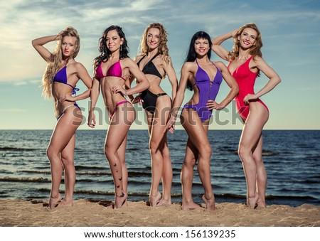 Five beautiful and sexy ladies in bikini posing on the beach - stock photo