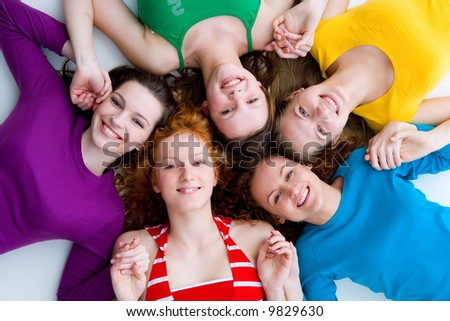 five beautiful girls laying on the floor smiling happily