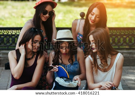 five beautiful young girls consider the bag in the park