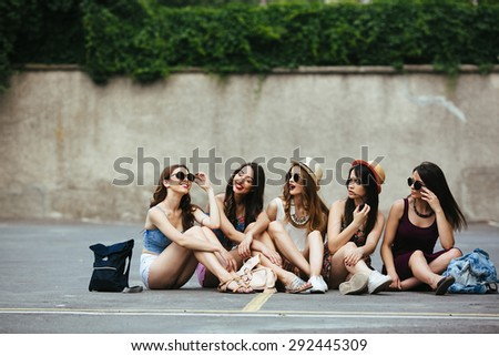 Five beautiful young girls relaxing in the city - stock photo
