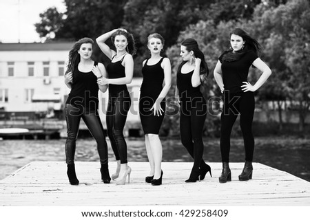 Five beautiful young sexy girls models in black tight dress posing on pier. Black and white photo