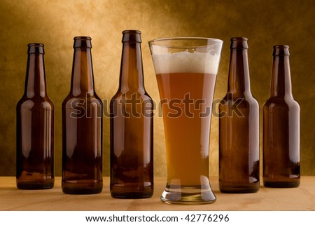 Five beer bottles and a glass of beer