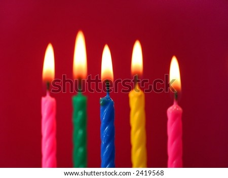 Five birthday candles.  Focus on the foremost (blue) candle. - stock photo