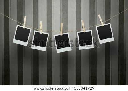 Five blank photographs hanging on a clothesline over vintage striped background with clipping path for the inside of the frames - stock photo