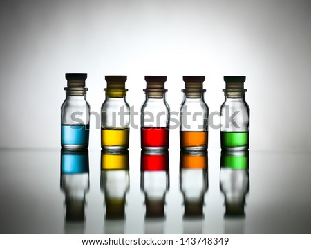 Five bottles with diverse colors of content reflected on a table - stock photo