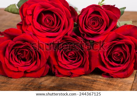 Five bright red roses on a wooden table - stock photo