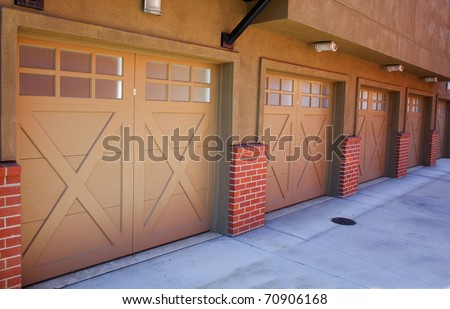 Five brown garage doors in perspective as part of an apartment complex - stock photo