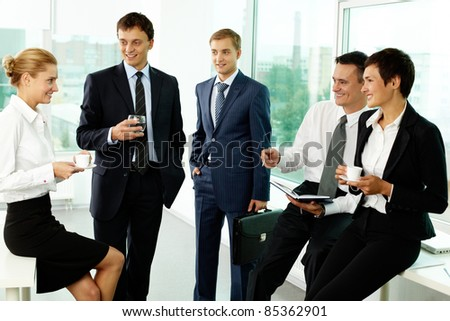 Five business colleagues communicating at break - stock photo