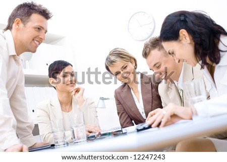 Five business colleagues sitting around table and working together, smiling. - stock photo