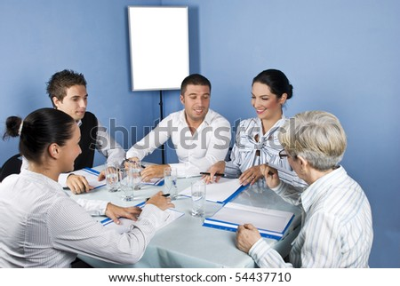 Five business people around a table at meeting laughing together and looking to paperwork of a businesswoman,blank chart or white board in background were you can type your text - stock photo
