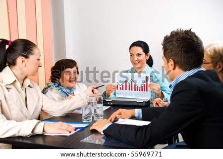 Five business people around a table having a conversation about sales while a businesswoman holding a diagram or a financial graph - stock photo