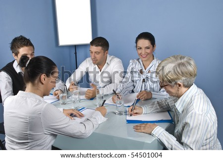Five business people at meeting have a discussion and they are cheerful and laughing together