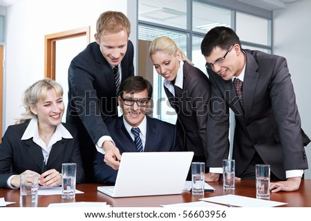 Five business people in suits discussing something with laptop