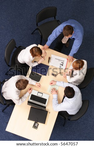 five business people meeting - boss speech .Businesspeople gathered around a table for a meeting, brainstorming. Aerial shot taken from directly above the table. - stock photo