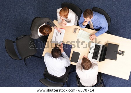 five business people meeting - Businesspeople gathered around a table for a meeting, brainstorming. Aerial shot taken from directly above the table. - stock photo